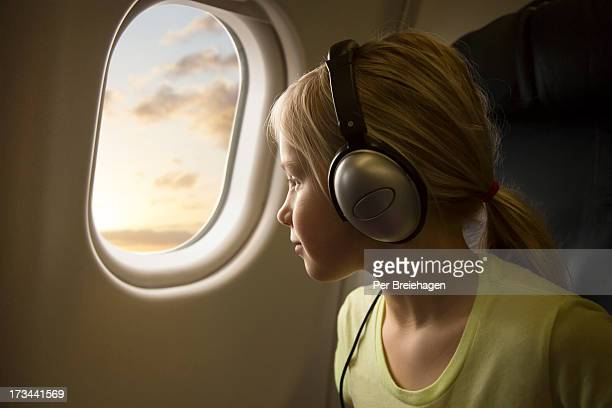 a girl in an airplane looking out of the window