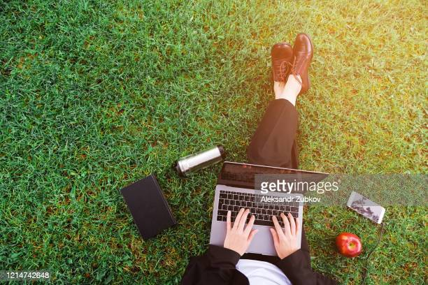 a girl in the park sitting on the grass and working on a laptop, a woman's hands on the keyboard. near mobile phone, apple, notebook. student studying outdoors. distance learning concept - palm sunday photos et images de collection
