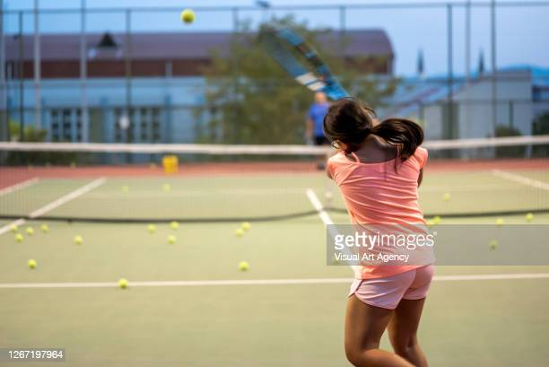 a girl is shooting backhand to her coach on the hardcourt focus on foreground - tennis tournament stock pictures, royalty-free photos & images