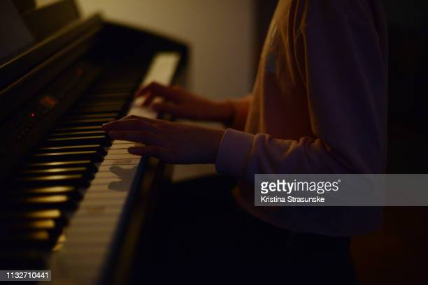 a girl playing piano - kristina strasunske stock photos and pictures