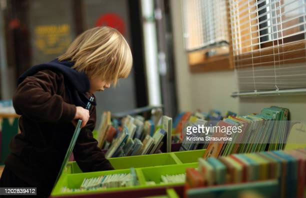 a girl standing by a drawer full of books in a library - knowledge is power stock pictures, royalty-free photos & images