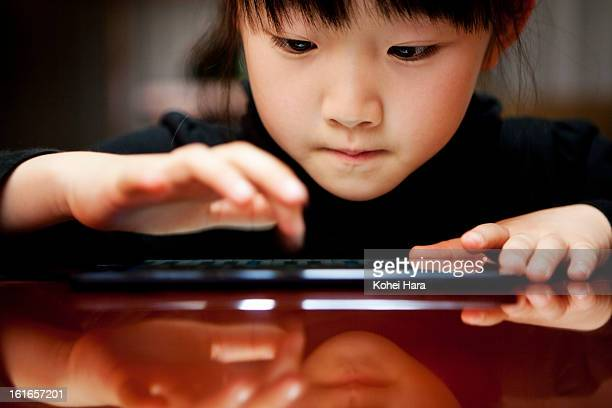 a girl using a digital tablet - 教育 ストックフォトと画像