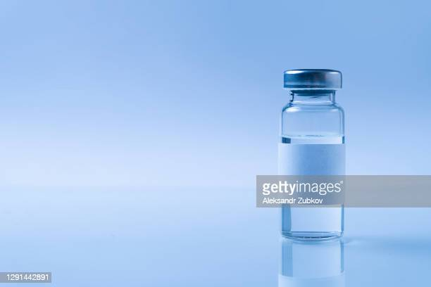 a glass medical bottle or ampoule with a vaccine for covid-19 or for colds and flu on a white background. the concept of treatment and prevention of the spread of infection, virus and pneumonia. - バイアル ストックフォトと画像