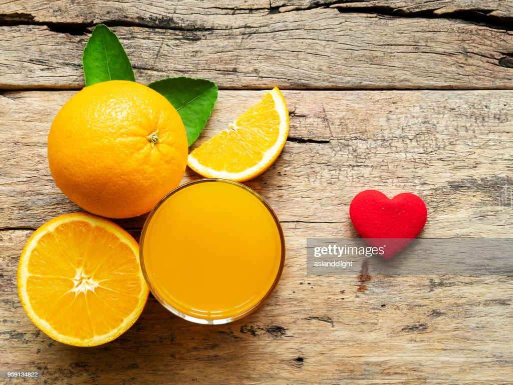 a glass of fresh orange juice and group of fresh orange fruits with green leaves, on wooden background with red heart shape. vitamin C and fruit product display or montage, studio shot : Stock Photo