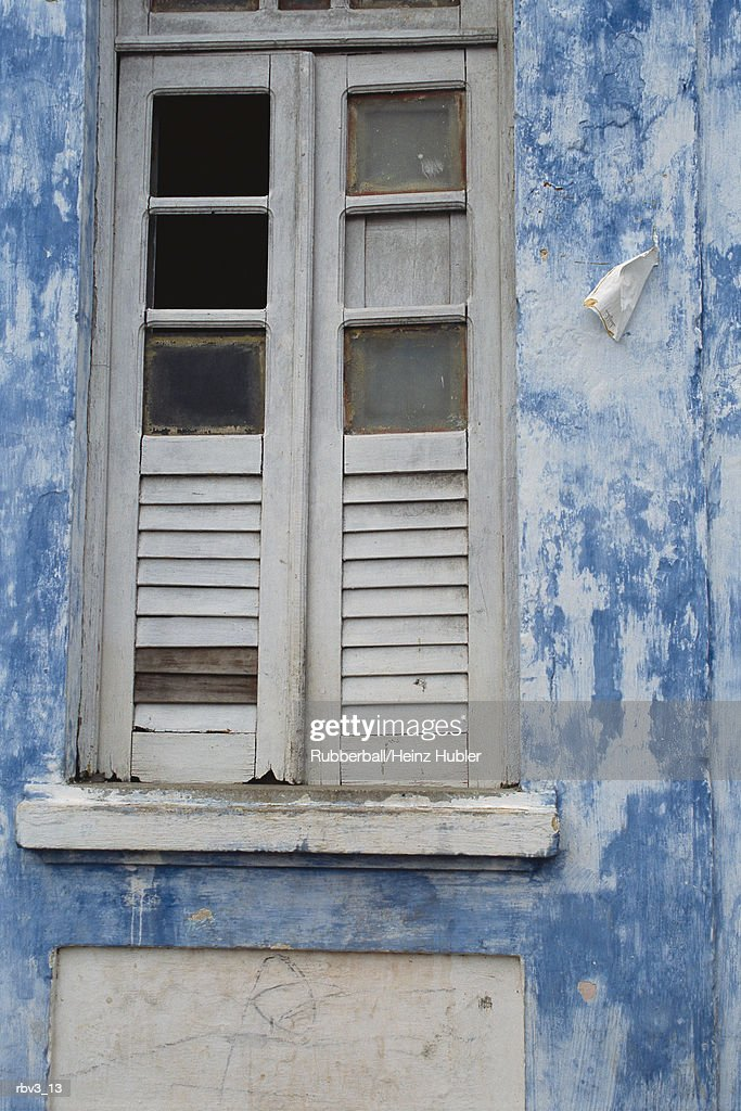 a glass window with shutters stands on a weathered blue and white painted wall : Foto de stock