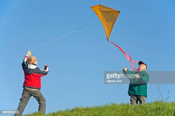a grandfather and his grandson are flying a selfmade kite together / families / family / people / children / kids / boy / grandad / grandpa / autumn...