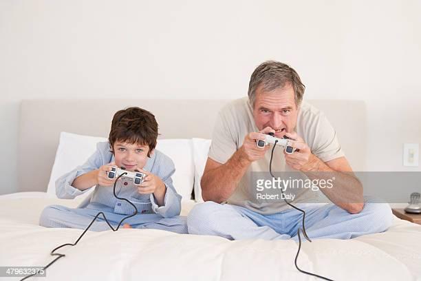 Einen Großvater Spielen von Videospielen mit seinem Enkel im Bett