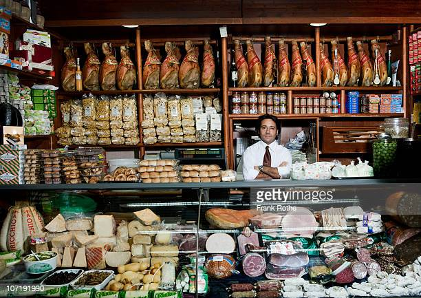 a grocer behind his counter in his shop - cultura italiana foto e immagini stock