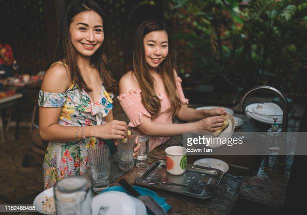 a group of asian chinese ladies cleaning dishes after dinner party at the kitchen - messy house after party stock pictures, royalty-free photos & images