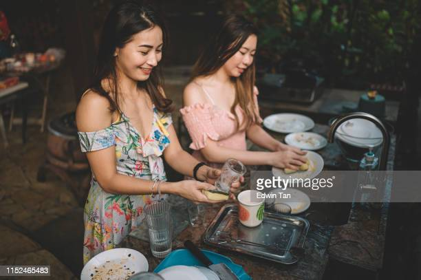 a group of asian chinese ladies cleaning dishes after dinner party at the kitchen - cleaning after party stock pictures, royalty-free photos & images