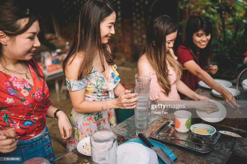 a group of asian chinese ladies cleaning dishes after dinner party at the kitchen : Stock Photo