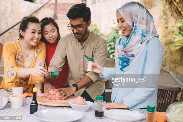 un grupo de asia multi-ética jóvenes adultos reunidos en villa durante el fin de semana para la escapada de la ciudad disfrutando de una sesión de barbacoa y preparando comida - malasia fotografías e imágenes de stock