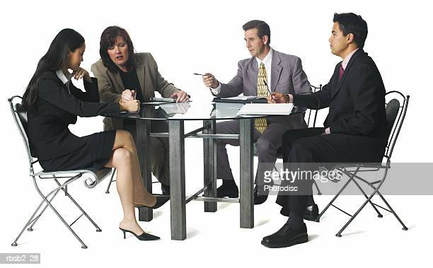 a group of business people sit around a table for a staff meeting