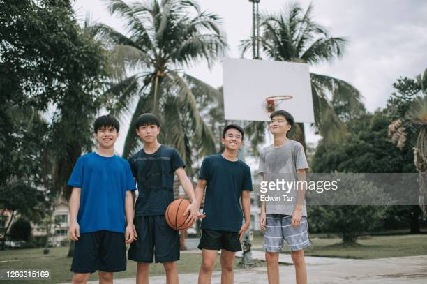 a group of chinese teenage boys at basket ball court having bonding time together after the game looking at camera