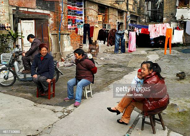 A group of Chinese women sitting in a yard minding babies and chatting as their washing dries, taken down one of the small lanes in Shanghai and...