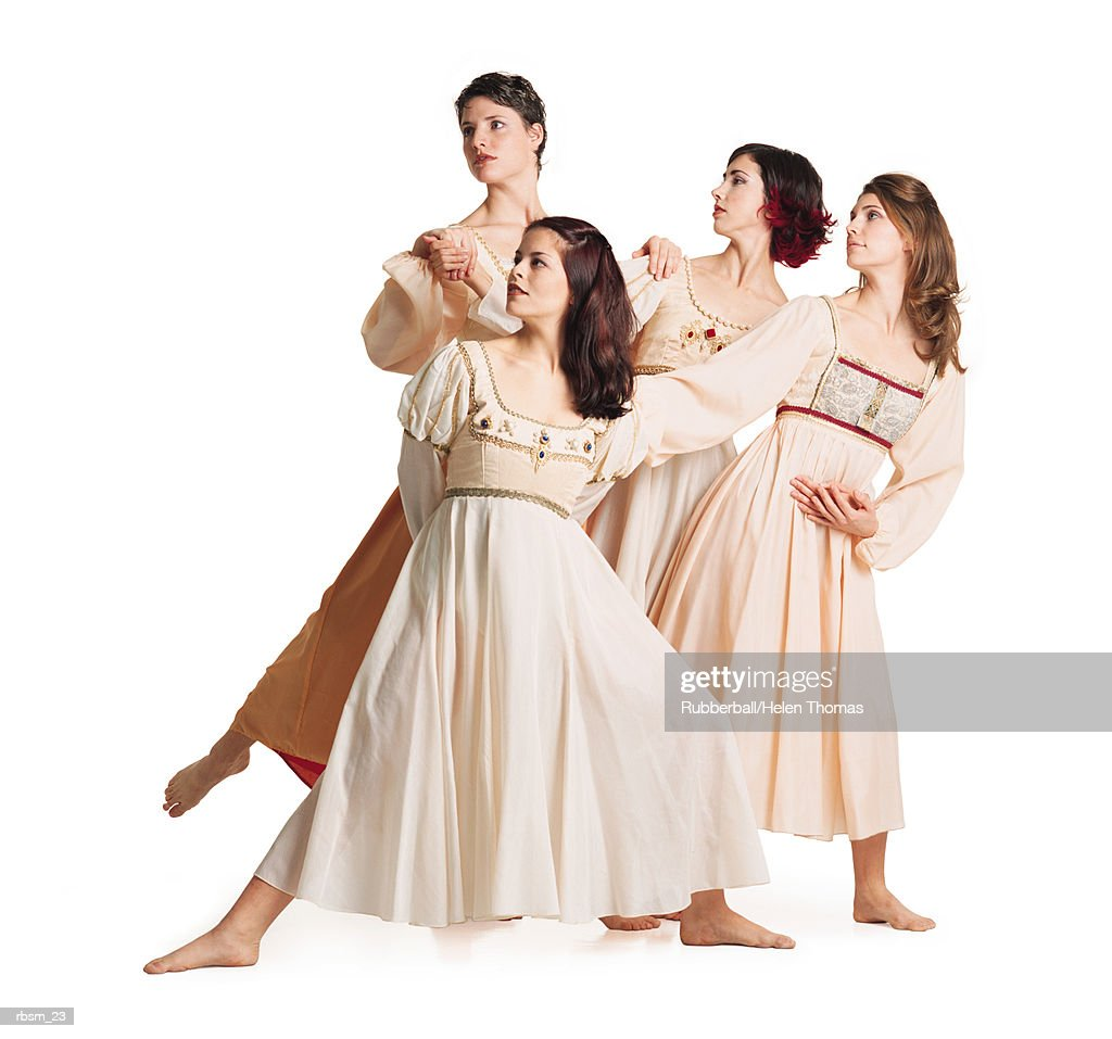 a group of four young caucasian female dancers in flowing dance costume dresses pose together with their legs extended forward : Foto de stock