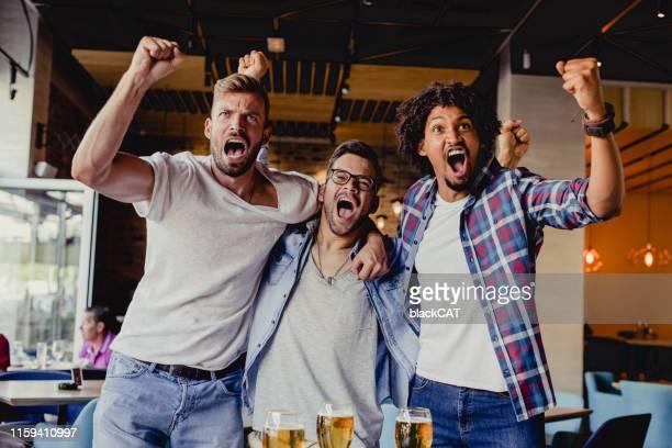 um grupo de amigos está assistindo a um jogo de esportes no pub enquanto bebe cerveja - fazer um gol - fotografias e filmes do acervo