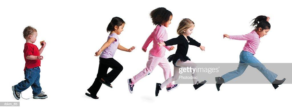 a group of girls run forward as a little boy strolls slowly behind them : Stock Photo
