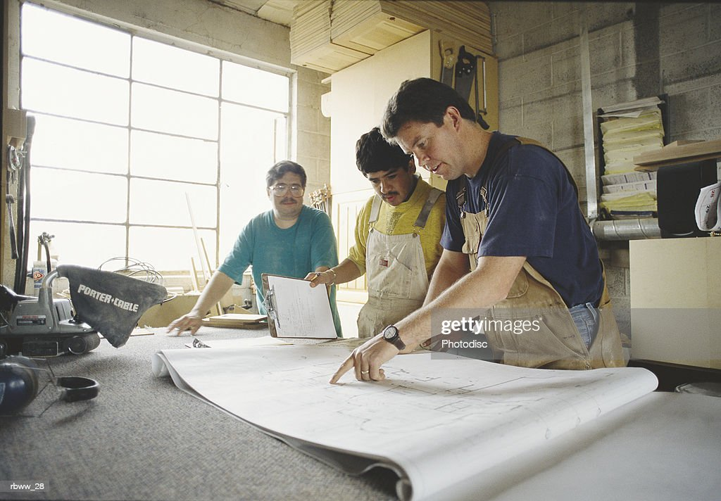 a group of men study building plans : Foto de stock