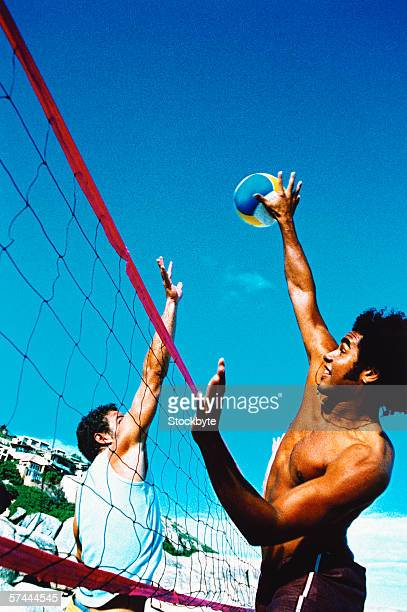 a group of people playing volleyball on the beach - beachvolleybal stockfoto's en -beelden
