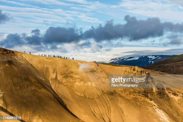 a group of people walking on the ridge of a rhyolite hills in front of a large glacier - austurland stock-fotos und bilder