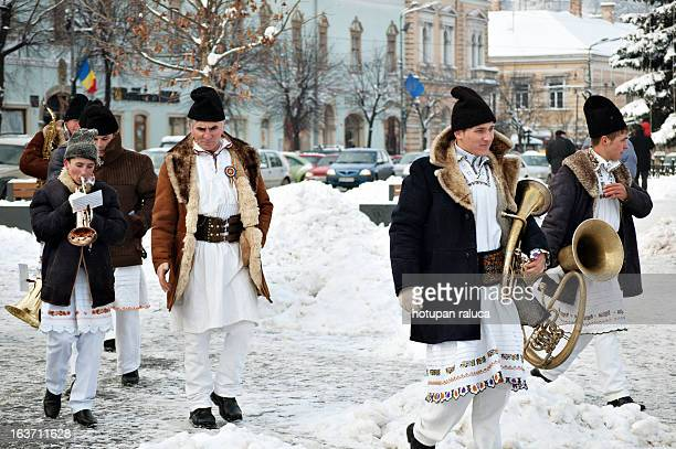 CONTENT] a group of romanian musician boys wearing traditional costumes after performing traditional carols in a public square in cluj napoca romania