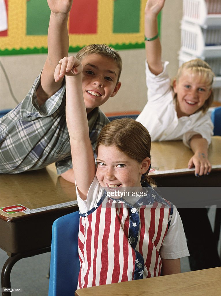 a group of students at their desks enthusiastically raise their hands to answer a question : Stockfoto