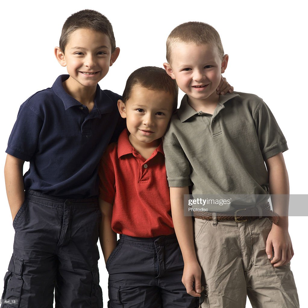 a group of three caucasian child brothers put their arms around each other and smile at the camera : Foto de stock