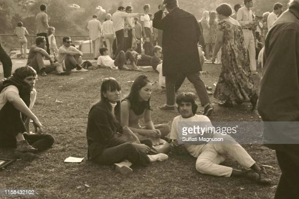 A group of three on the grass, a couple with woman in a mumu walking by, and several young men sitting on the grass taking it all in at the 1st...