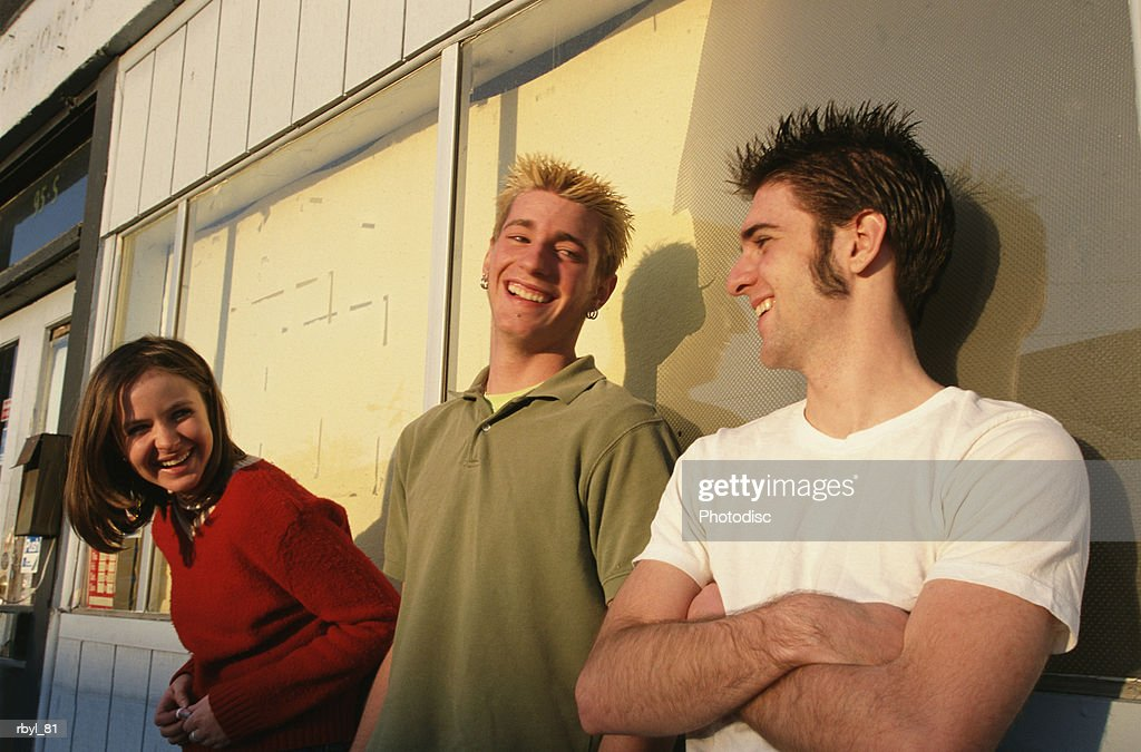 a group of two young men and a young woman are standing outside a city storefront laughing and talking to eachother : Foto de stock
