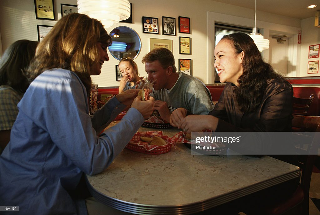 a group of young adults are sitting in a booth of a diner or cafe laughing and talking to eachother : Foto de stock