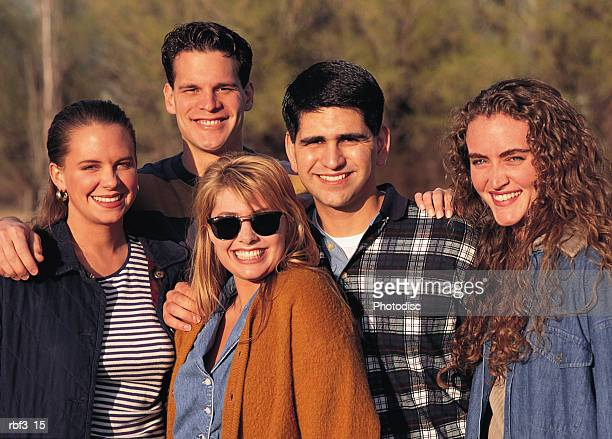 a group of young adults gather together in an area of trees as the sun shines around them - squinting stock photos and pictures
