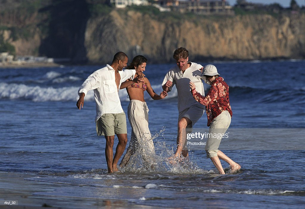 a group of young adults is playing in the ocean waves and splashing one another : Foto de stock