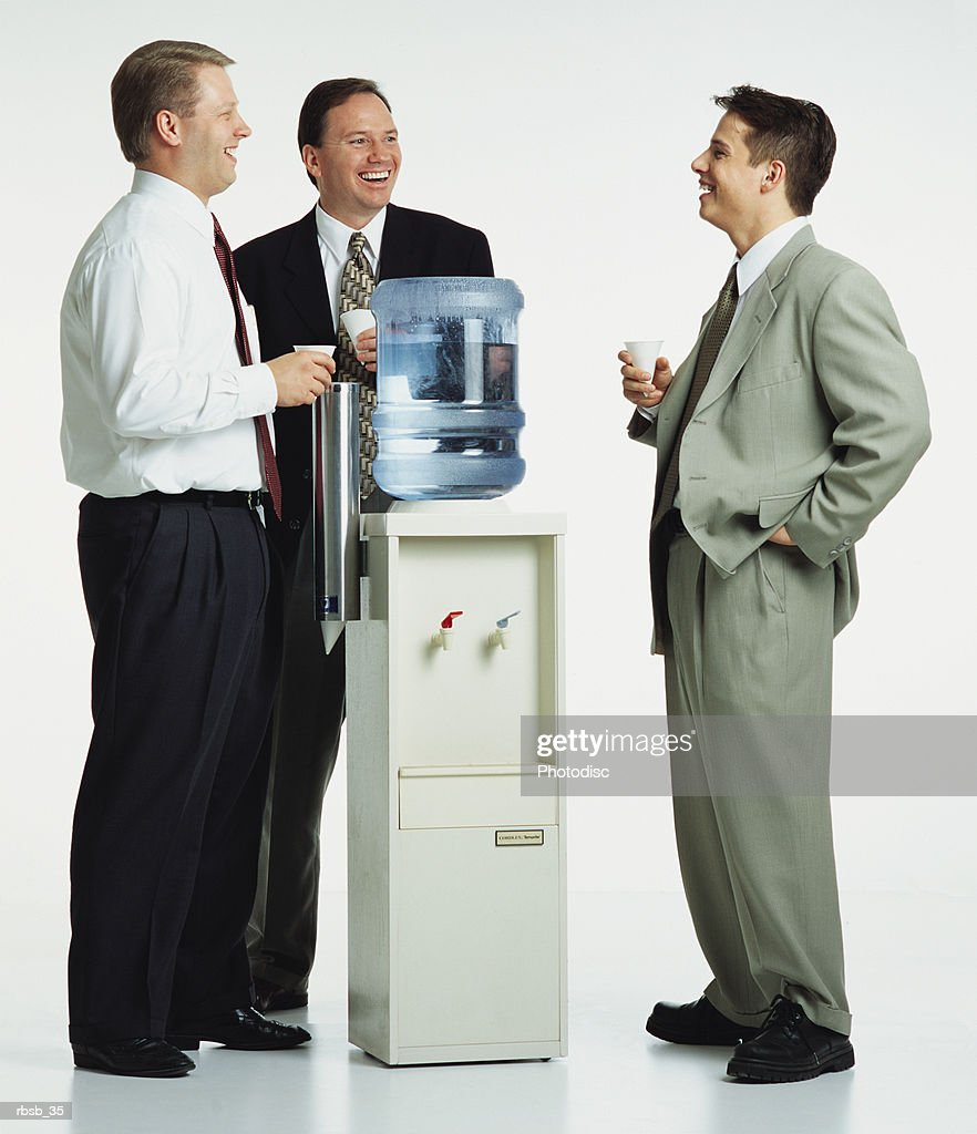 a group of young caucasian businessmen are standing around a watercooler lauging and conversing with eachother : Foto de stock