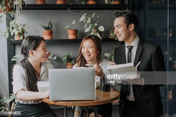 een groep jonge uitvoerende macht die snelle lunchpauze in de ruimte van de lounge tijdens lunchtijd met lunchdoos cosharing plaats coworking heeft - zuidoost aziatische etniciteit stockfoto's en -beelden