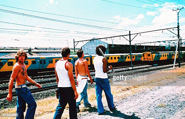a group of young men walking along the railway tracks with a baseball bat