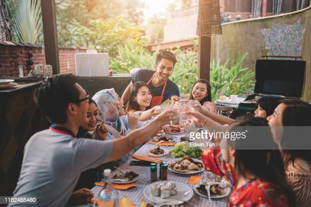 un grupo de amigos multi ética de ph que tienen un brindis de celebración en la zona de comedor en la villa durante el fin de semana escapada - malasia fotografías e imágenes de stock
