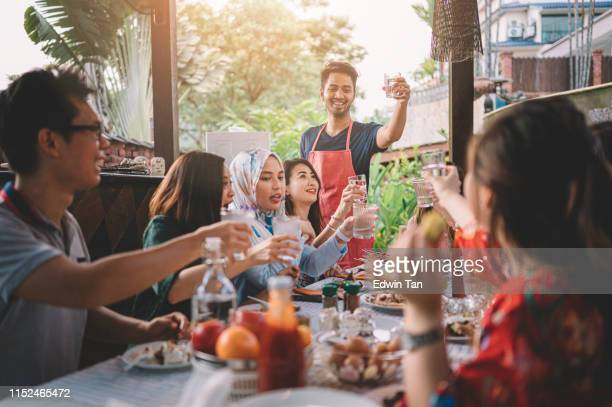 a group ph multi ethic friends having a celebration toast at the dinning area at villa during weekend city break - malaysian culture stock pictures, royalty-free photos & images