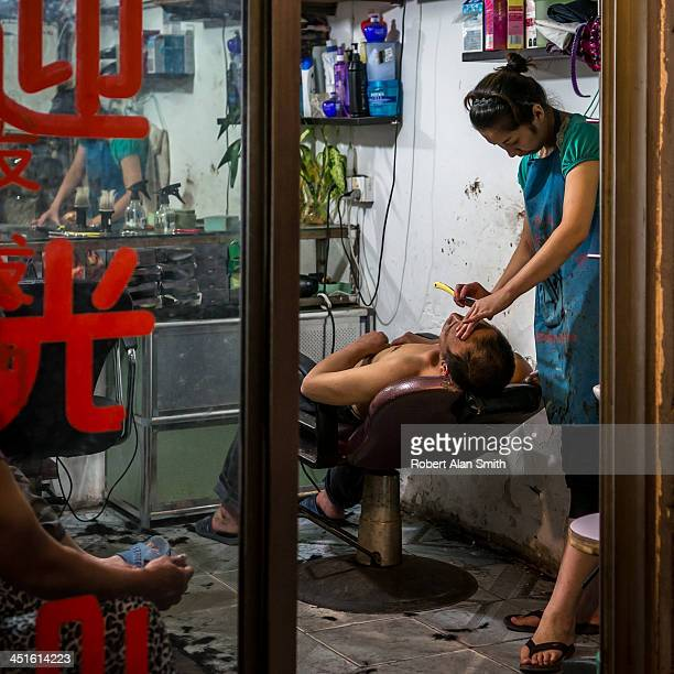 A guy having a shave with a cut throat razor in a small barber shop down one of the narrow lanes in down town Shanghai