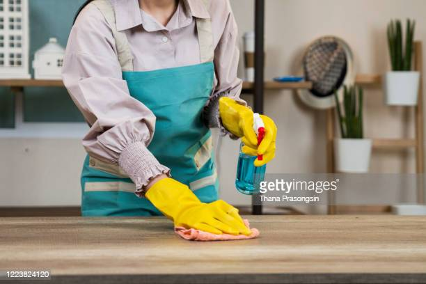 a hand wiping table surfaces - housework stock pictures, royalty-free photos & images