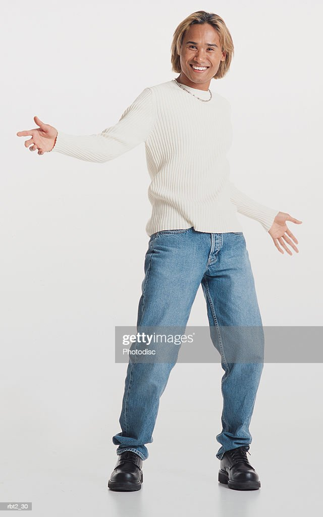 a handsome asian young man with bleached hair stands gesturing expressively with his hands and smiling happily at the camera : Foto de stock