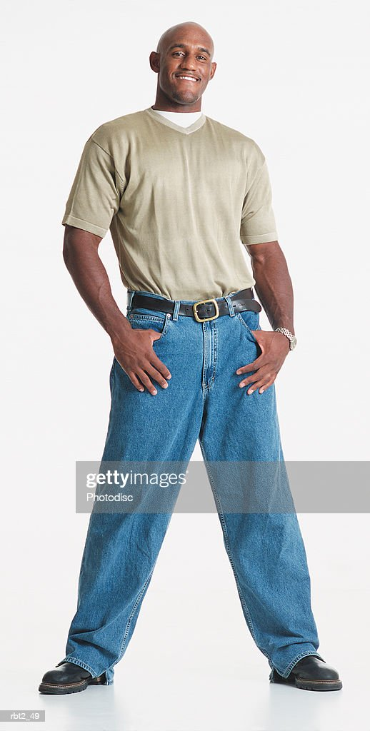 a handsome bald african american man wearing a v-neck teeshirt stands relaxed with legs apart and thumbs in his jeans pockets as he smiles : Foto de stock
