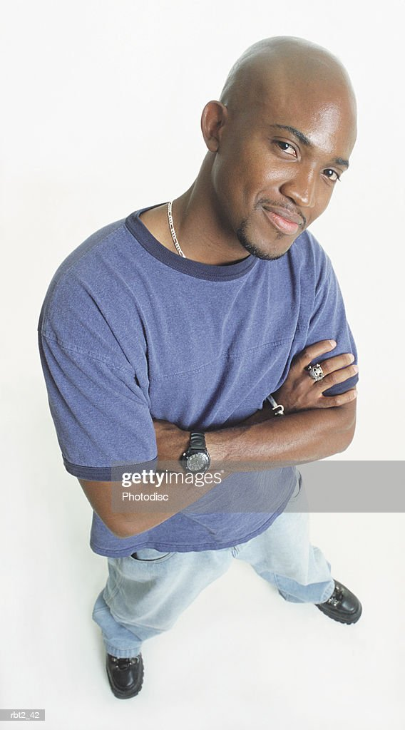 a handsome bald black young man with a goatee wearing a blue teeshirt and jeans is standing with arms crossed looking up at the camera and grinning : Foto de stock