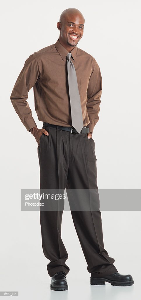 a handsome bald black young man with a goatee wearing slacks and a brown dress shirt and ties stands with hands in pockets and smiles at the camera : Foto de stock
