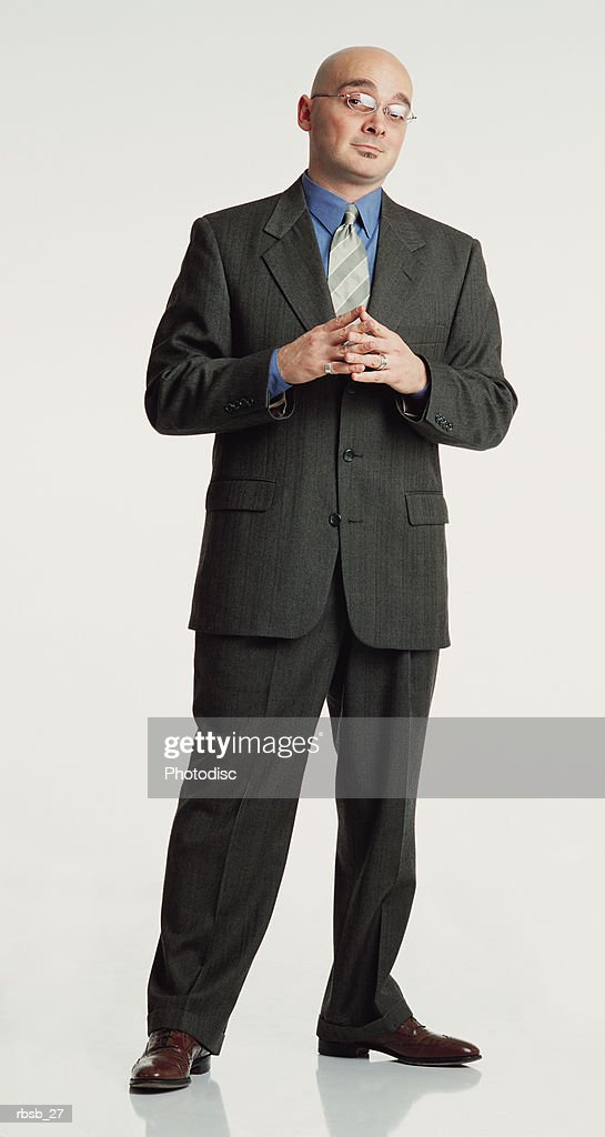 a handsome bald caucasian man in glasses is dressed in a grey suit stands with his hands together while looking into the camera with serious expression on his face : Foto de stock