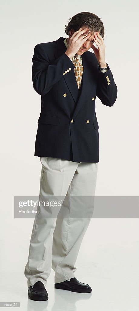 a handsome caucasian male with long dark hair dressed in a blue blazer and tan pants stand with his head in his hands looking worried : Foto de stock