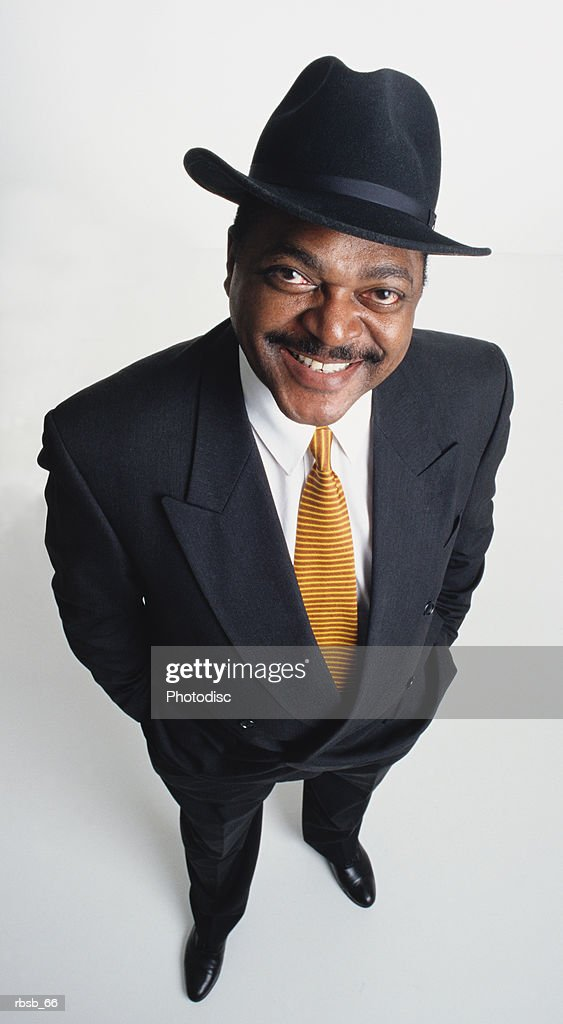 a handsome middle aged african american man with black hat and dark business suit looking up into the camera with his hands in his pockets : Foto de stock