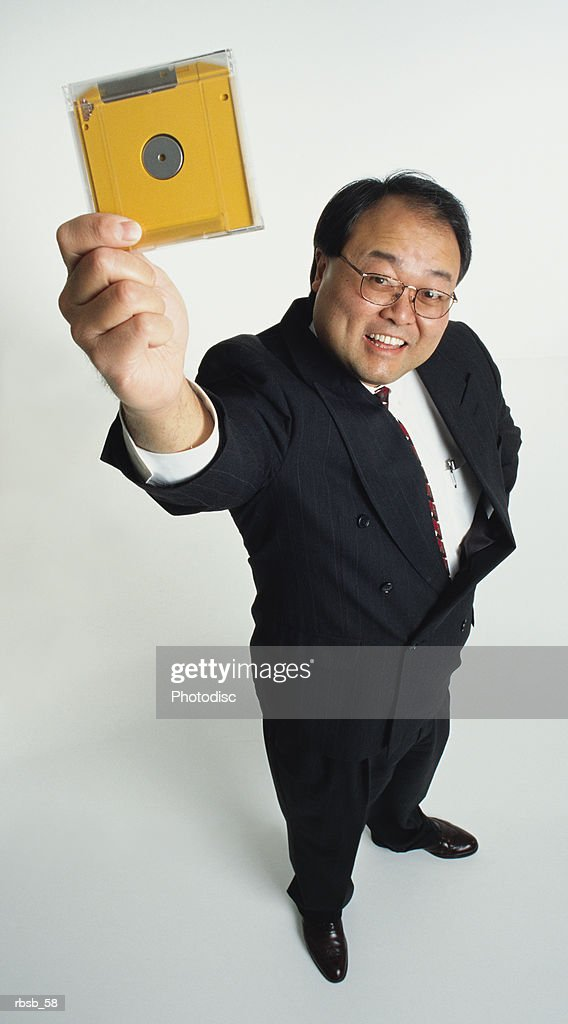 a handsome middle aged asian businees man with glasses dressed in a business suit looking up into the camera holiding up a yellow zip disk : Foto de stock