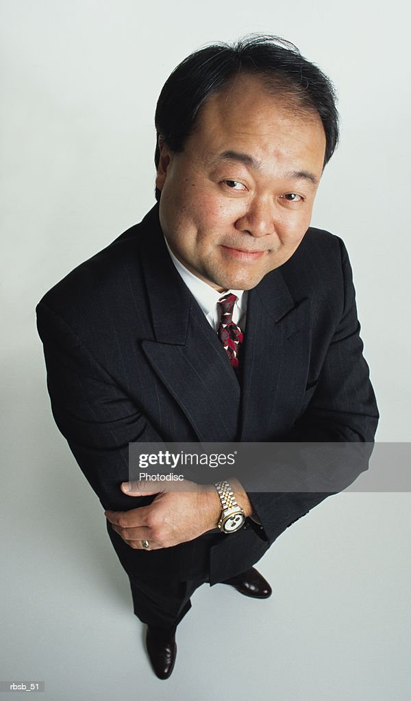 a handsome middle aged asian businessman in a dark business suit is looking into the camera with his arms crossed : Foto de stock