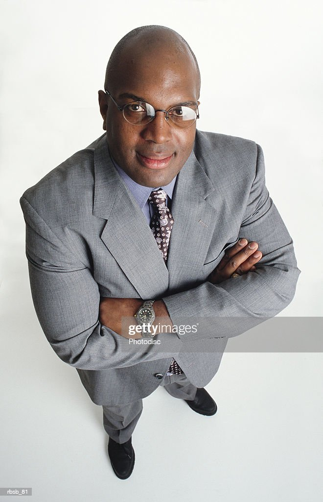 a handsome middle aged bald african american man in a light grey business suit stands looking up at the camera with his arms crossed : Foto de stock